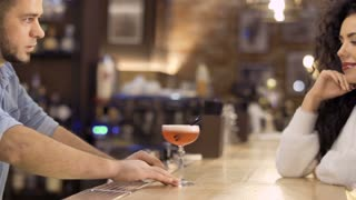 Bartender gives beautiful woman an exotic cocktail in the pub