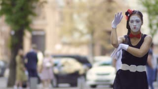 Beauitiful girl mime gesticulating hands at blurred street background