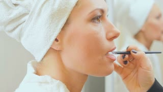 Beautician applies a lip gloss on lips of young woman