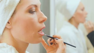 Beautician applies a lip gloss on woman's lips