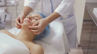 Beautician makes a facial massage for patient in beauty clinic