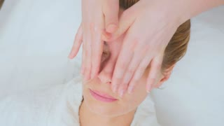 Beautician makes facial massage with cream to young woman