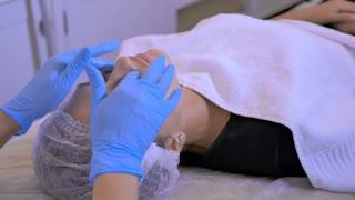 Beautician making a facial massage in a beauty salon