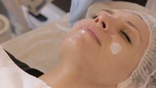 Beautician rubs the cream on woman's face