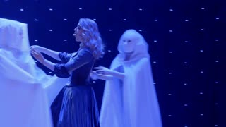 Beautiful actress sings song and dances with strangers in cloaks on the scene