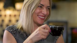 Beautiful adult woman drinking coffee at restaurant