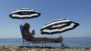 Beautiful adult woman in bikini lays on deck chair on seashore and drinks water