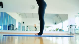 Beautiful blonde girl practicing yoga in the sport's gym