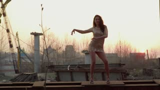 Beautiful brunette dancing at sunset standing at metal construction