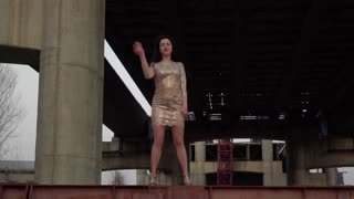 Beautiful brunette dancing at the background of abandoned bridge
