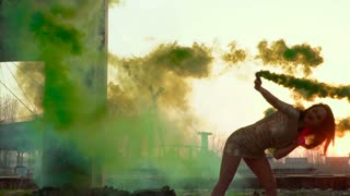 Beautiful brunette in dress dancing with green smoke in slowmotion