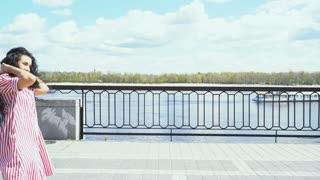 Beautiful brunette in dress is walking on the embankment near the river