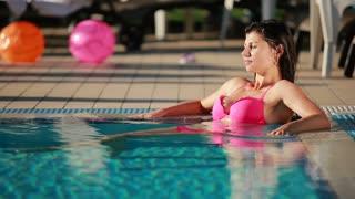 Beautiful brunette in pink swimsuit sunbathe in the swimming pool
