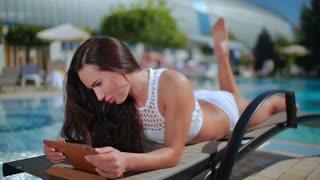 Beautiful brunette in white bikini relax on deck chair near swimming pool