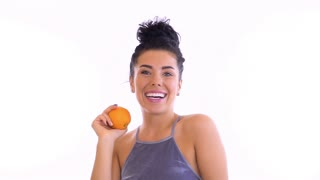 Beautiful brunette plays with orange at white background