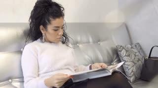 Beautiful brunette read magazine at the sofa