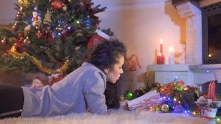 Beautiful brunette read the book near Christmas tree