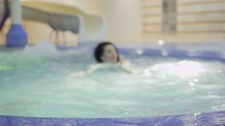 Beautiful brunette swims in a blue pool
