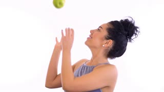 Beautiful brunette throws up green apple and laughing at white background