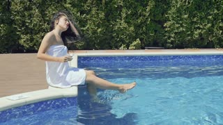 Beautiful brunette with cocktail splashes water in blue pool