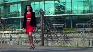 Beautiful businesswoman in red dress dancing near business center