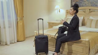 Beautiful businesswoman talks on phone in a hotel room