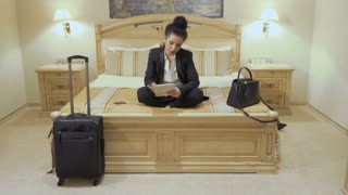 Beautiful businesswoman with red lips uses digital tablet in a hotel room