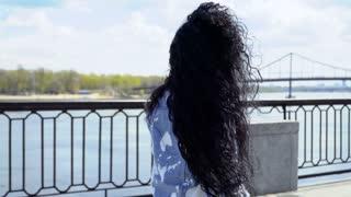 Beautiful curly brunette walks at embankment