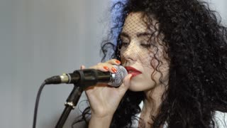 Beautiful curly brunette with veil on face sings in microphone