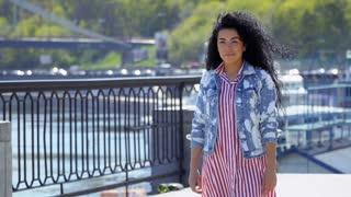 Beautiful dreaming girl walks at embankment