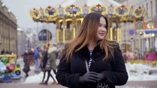 Beautiful fat woman stands against carousel background