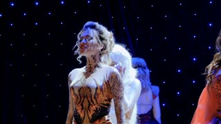 Beautiful fire girl sing song on stage in theatre