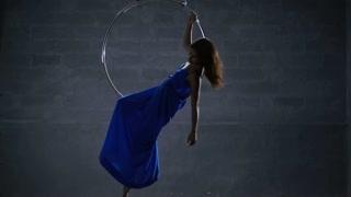 Beautiful gentle girl in blue long dress spins in the aerial hoop