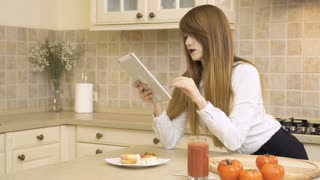 Beautiful girl eats sandwich and uses tablet at the kitchen