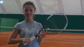 Beautiful girl holding a tennis racket and smiling on the court