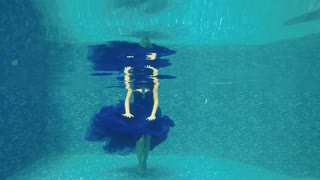 Beautiful girl in long blue dress poses for camera underwater in pool
