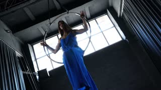 Beautiful girl in long dress is moving in the aerial hoop at window background