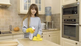 Beautiful girl in protective gloves clean table at the kitchen with detergent