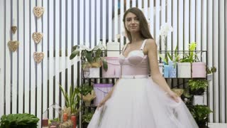 Beautiful girl in white dress is circling around herself - slowmotion