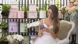 Beautiful girl in white dress sit on vintage chair in flower shop and uses phone