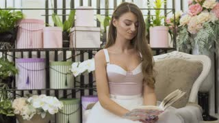 Beautiful girl in white dress writes in notebook sitting in vintage chair