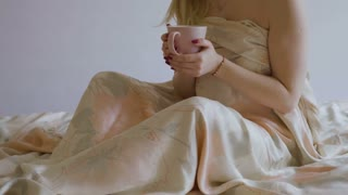 Beautiful girl just woke up and drinks coffee in the bed