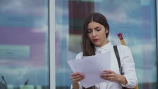 Beautiful girl looks business papers
