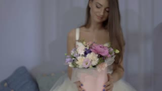 Beautiful girl presents festive box with bouquet of flowers