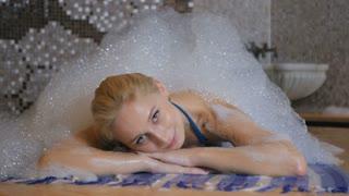 Beautiful girl relaxing under the foam in the Turkish bath