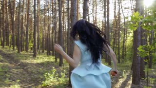 Beautiful girl wearing blue dress and holding apple, running in the forest