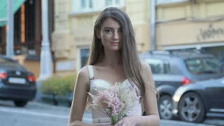 Beautiful girl with flowers near blurred road