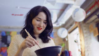 Beautiful korean woman enjoys traditional korean dish and shows thumb up