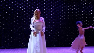 Beautiful lady in white dress sing sensual song on the stage