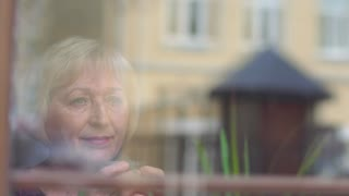 Beautiful mature woman drink coffee near the window